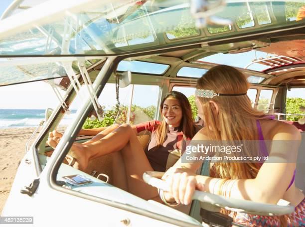 Women sitting in van on beach