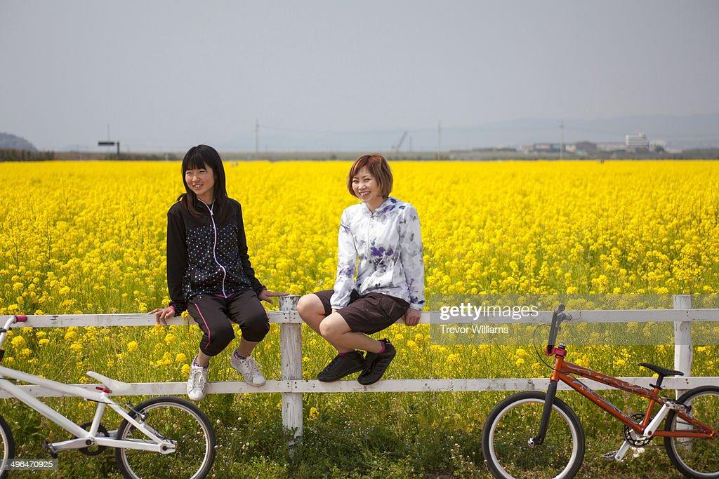 2 women sitting on a fence in a field of flowers