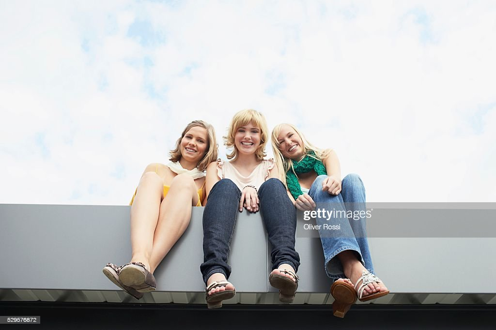 Women Sitting on a Ledge : Stock Photo