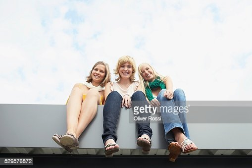 Women Sitting on a Ledge : Photo