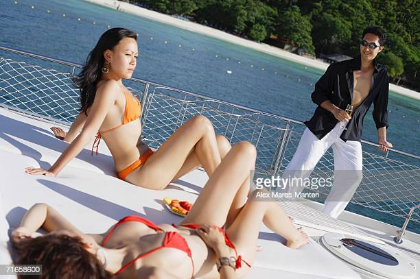 Women sitting on boat deck, man standing next to railing, holding champagne glass