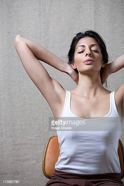 Women sitting on chair with hands behind head, eyes closed