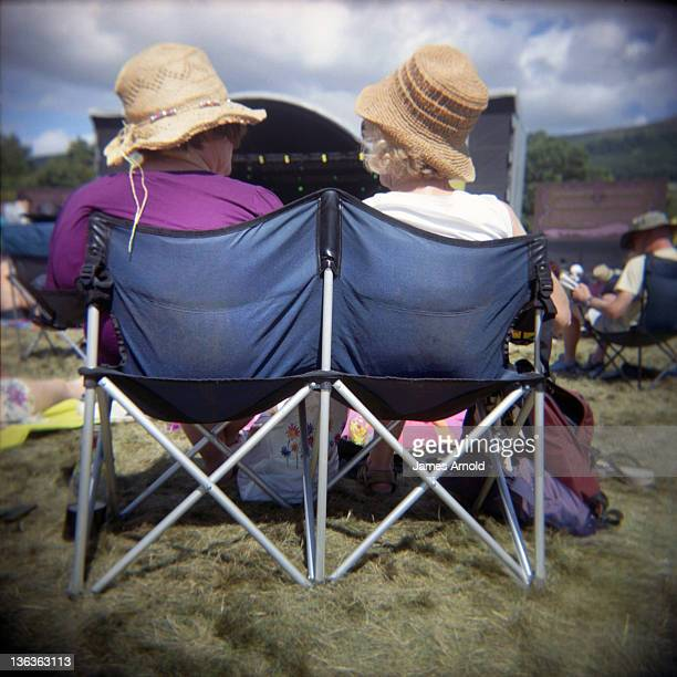 Women sitting on chairs at music festival