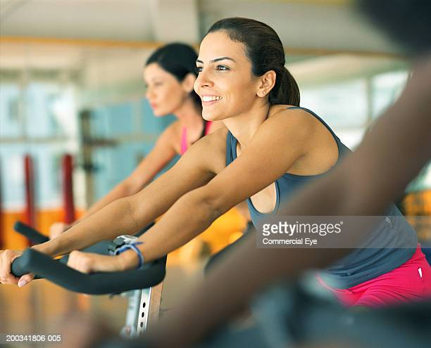 Women sitting on spinning bikes in gym, side view