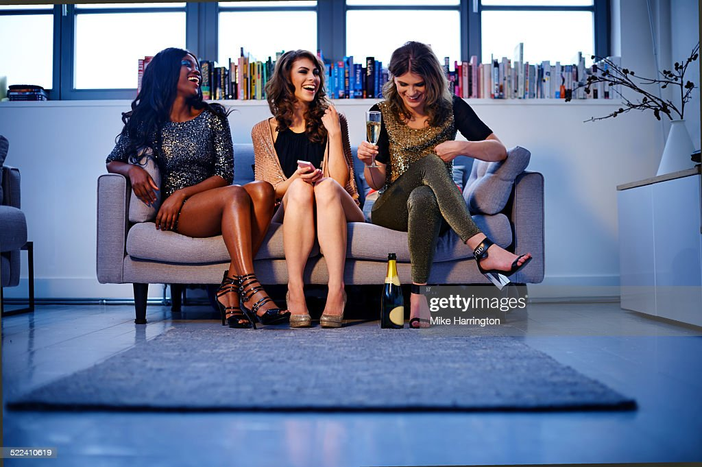 Women sitting on sofa enjoying drinks and laughing : Stock Photo
