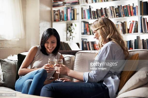 Women sitting on sofa having fun