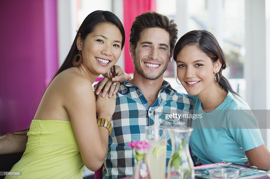 Women sitting with hand on a man's shoulders in restaurant : Stock Photo