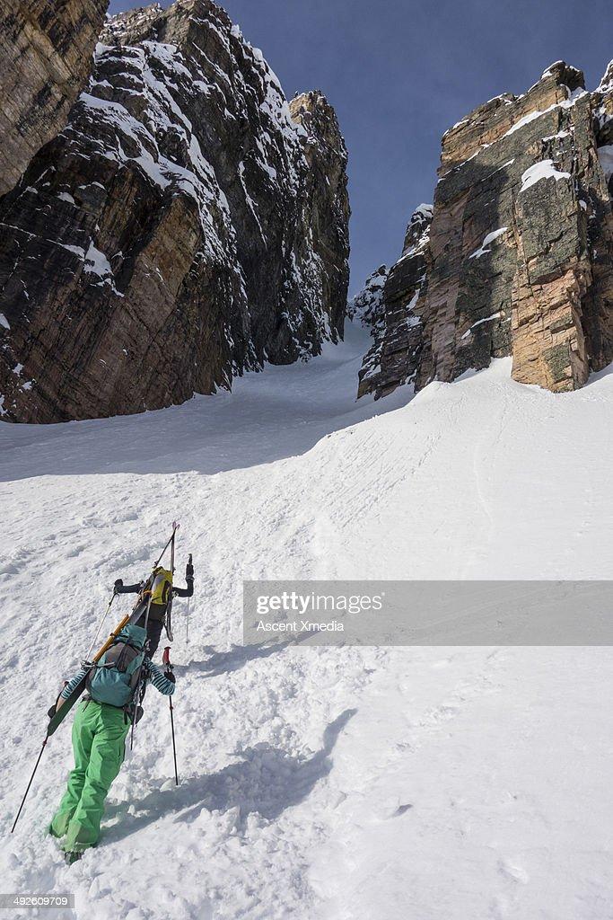Women ski mountaineers climb snow gully, with skis
