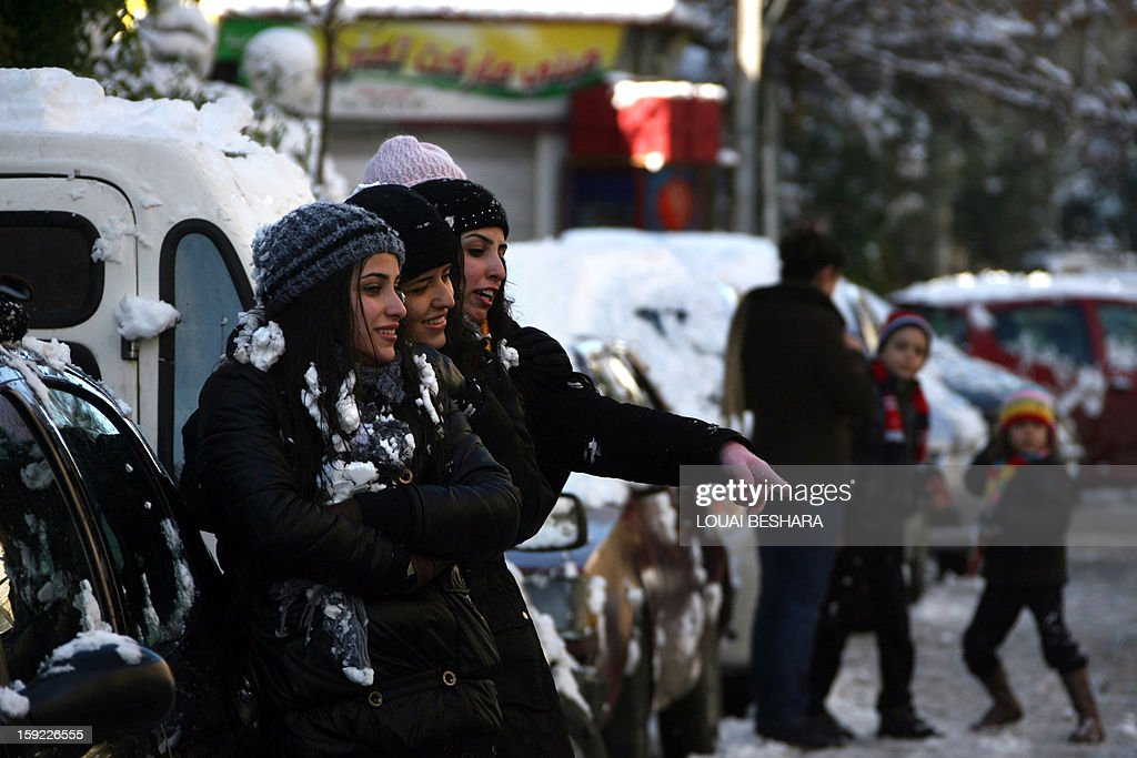 Women smile in a street covered with snow on January 10, 2013 in the Syrian capital of Damascus after heavy snow falls. Snow carpeted Syria's war-torn cities but sparked no let-up in the fighting, instead heaping fresh misery on a civilian population already enduring a chronic shortage of heating fuel and daily power cuts.
