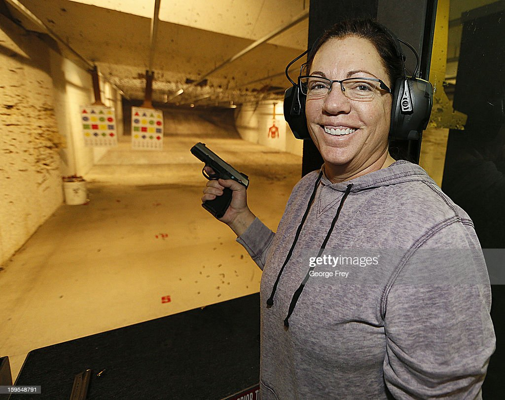 A women smiles after she fired a handgun at the 'Get Some Guns & Ammo' shooting range on January 15, 2013 in Salt Lake City, Utah. Lawmakers are calling for tougher gun legislation after recent mass shootings at an Aurora, Colorado movie theater and at Sandy Hook Elementary School in Newtown, Connecticut.