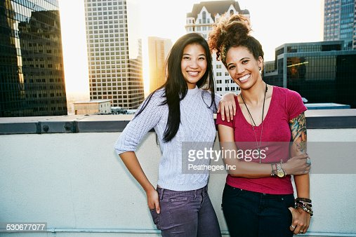 Women smiling on urban rooftop