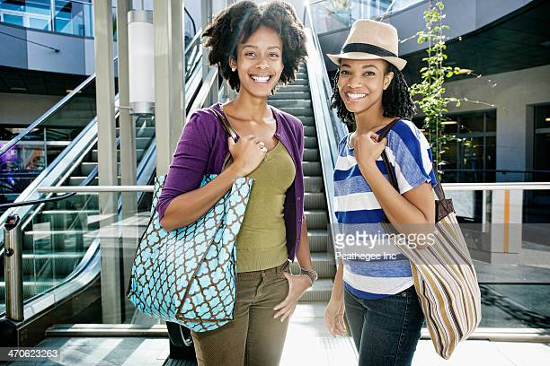 Women smiling together at outdoor mall