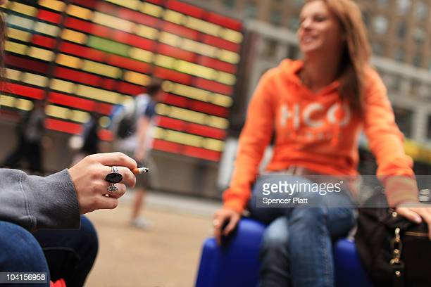 Women smoke in a Times Square pedestrian island on September 16 2010 in New York City New York City Mayor Michael Bloomberg has proposed a ban on...