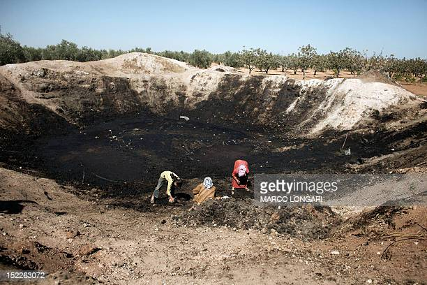 Women spread the waste of pressed olives mixed with water to let it dry in the sun in a field near the battled Syrian city of alBab on September 16...