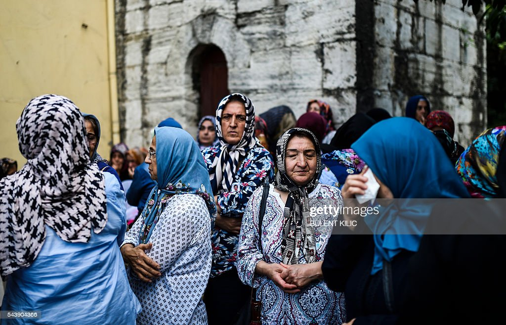 Women stand and look on as people gather for the funeral of Turkish teacher Huseyin Tunc in Istanbul on June 30, 2016 two days after the triple suicide bombing and gun attack occurred at Istanbul's Ataturk airport. The death toll from the triple suicide bombing and gun attack that occurred on June 28, 2016 at Istanbul's Ataturk airport has risen to 43 including 19 foreigners. The government has pointed the finger of blame at the Islamic State group and Turkish police rounded up 13 suspected IS jihadists in raids at 16 different locations across Istanbul on June 30. / AFP / BULENT