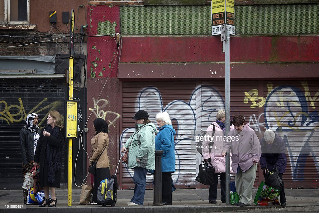 Women stand and wait in line at a bus stop on Thomas Street in Dublin, Ireland, on Saturday, March 16, 2013. Ireland's renewed competiveness makes it a beacon for the U.S. companies such as EBay, Google Inc. and Facebook Inc., which have expanded their operations in the country over the past two years. Photographer: Simon Dawson/Bloomberg via Getty Images