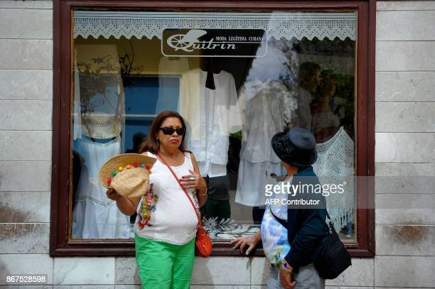 Women stand beside the window of a typical clothing store in Havana on October 27 2017 Almost drowned by the crisis of the 90s the emerging Cuban...