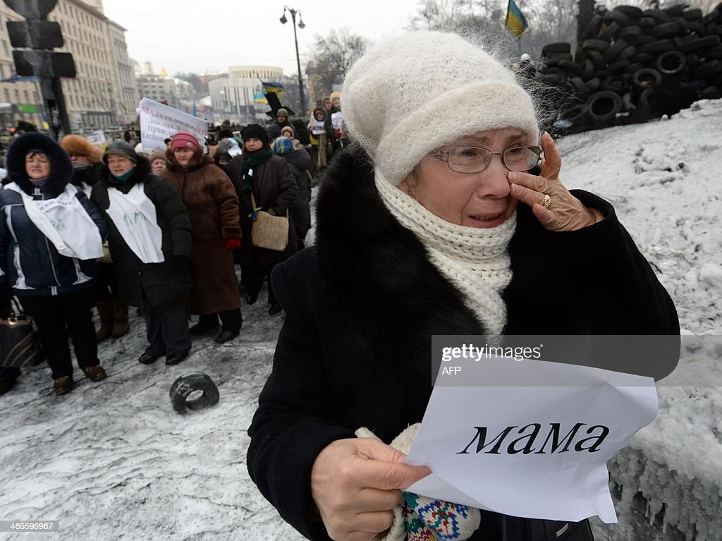 Women stand in front of riot police troops and hold placards reading Mother, urging riot police troops to stop fighting with protesters at the flashpoint Grushevsky Street in central Kiev on January 28, 2014. Ukrainian Prime Minister Mykola Azarov, who offered his resignation on Tuesday after months of pressure from the opposition, is a loyalist bureaucrat with a nasty temper who once told his critics to 'piss off'. MAXIMOV