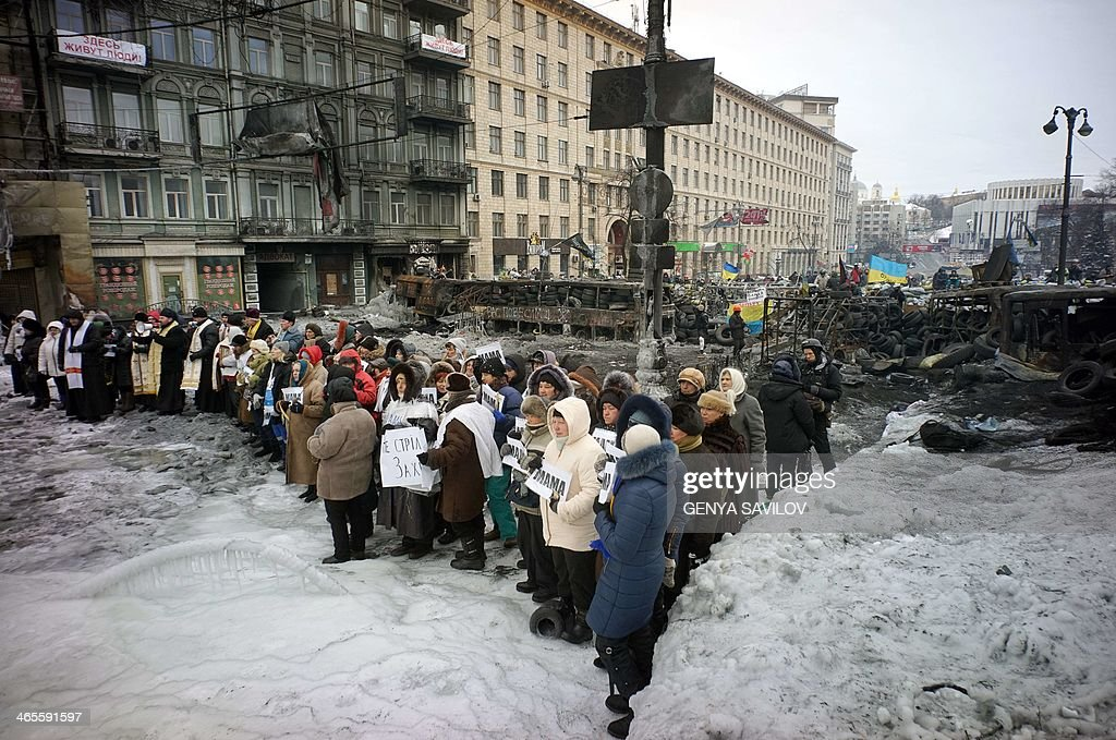 Women stand in front of riot police troops and hold the placards reading Mother, urging riot police troops stop fighting with protesters at the flashpoint Grushevsky Street in central Kiev on January 28, 2014. Ukraine lawmakers on Tuesday scrapped draconian anti-protest laws that have angered the opposition, in a move aimed at bringing a deadly two-month standoff to an end.