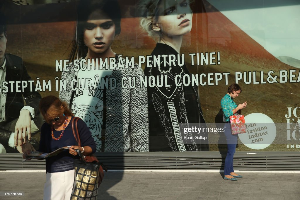 Women stand next to a fashion store display in the city center on September 6, 2013 in Bucharest, Romania. While the country's economic output has risen significantly since it joined the European Union in 2007, it still lags in infrastructure development and the fight against corruption.