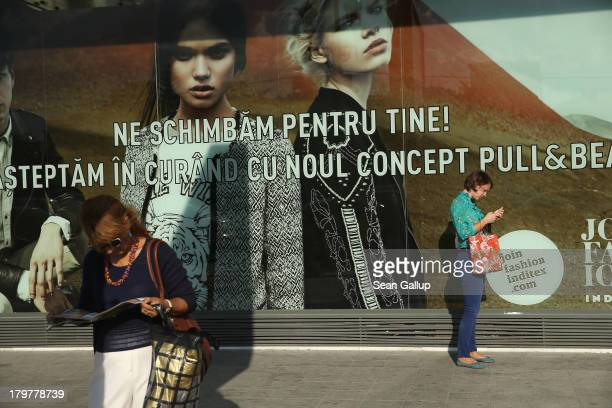Women stand next to a fashion store display in the city center on September 6 2013 in Bucharest Romania While the country's economic output has risen...