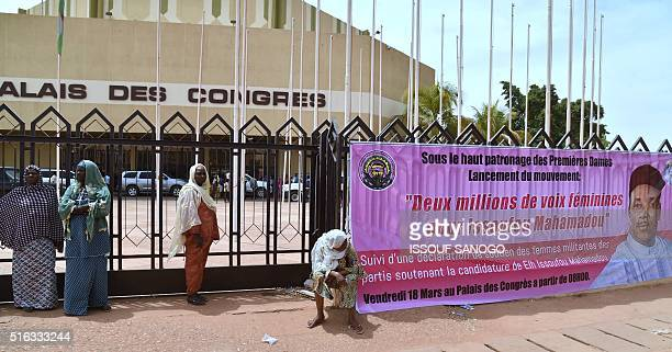 Women stand next to an electoral banner of Niger's incumbent President and candidate to his reelection Mahamadou Issoufou in front of the Palais des...