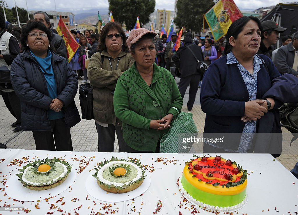 Women stand next to pies made with coca flour during a celebration for the reincorporation of Bolivia to the UN Convention Against Illicit Traffic in Narcotic Drugs in La Paz on January 14, 2013. 'The coca leaf is not any more seen as cocaine (..), it is a victory of our identity' said Bolivian President Evo Morales. AFP PHOTO/Jorge Bernal