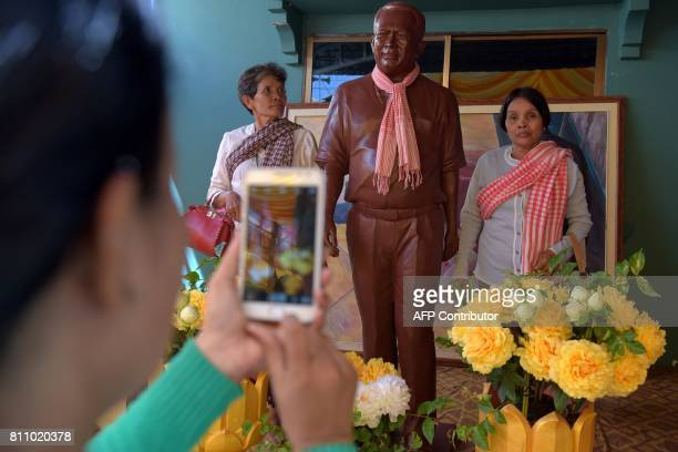 Women stand pose for a picture with a statue of Cambodian critic Kem Ley during the first anniversary of his murder at his mother's home in Takeo...