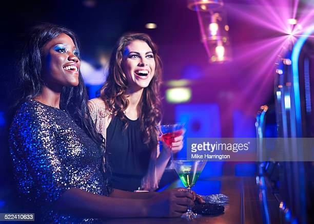 Women standing at bar in club, smiling