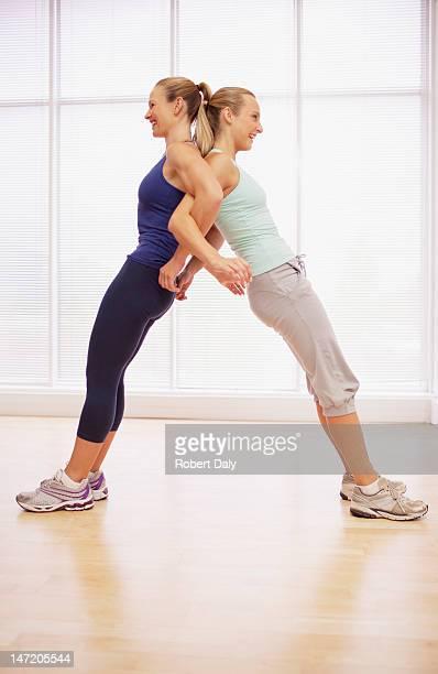 Women standing back to back in fitness studio