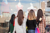 Rear view of a group of three women looking at a clothing store display