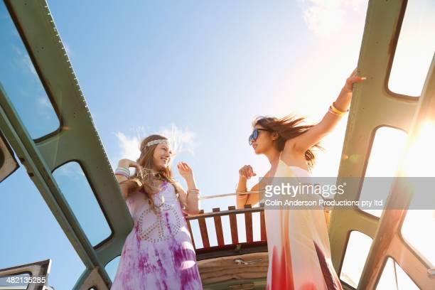 Women standing in sunroof of van