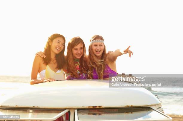 Women standing in van on beach