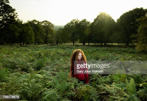 Women stands in grass ferns in city park : Stock Photo