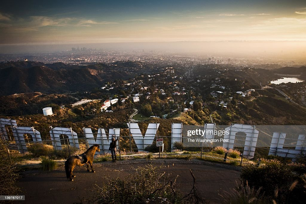 A women stops with her horse to photograph the famous Hollywood Sign over looking the Hollywood Hills on January 31 on Mount Lee in Griffith Park in...