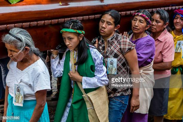 Women strain under weight of religious float in the streets of Antigua, Guatemala