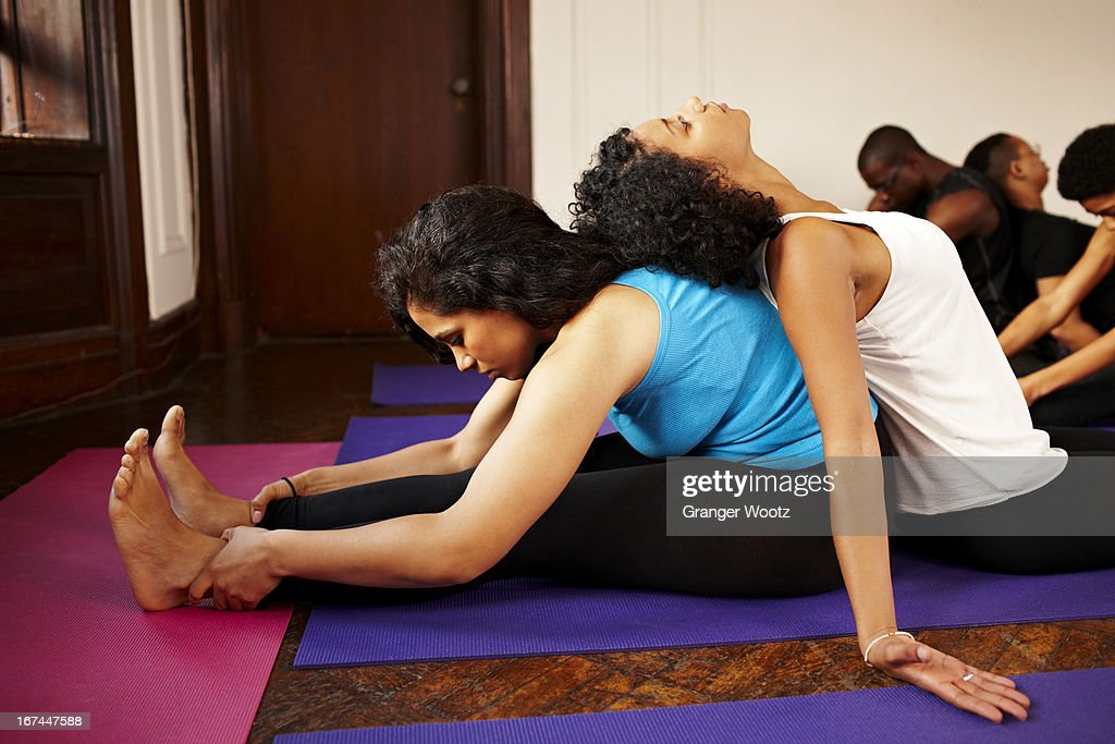 Women stretching together in yoga class : Stock Photo