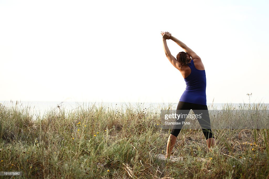 Women stretching with sea in the background : Stock Photo