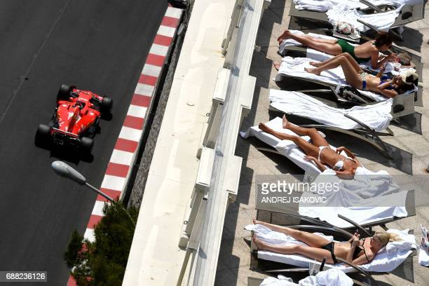 Women sunbath as Ferrari's German driver Sebastian Vettel steers his car during the second practice session at the Monaco street circuit on May 25...