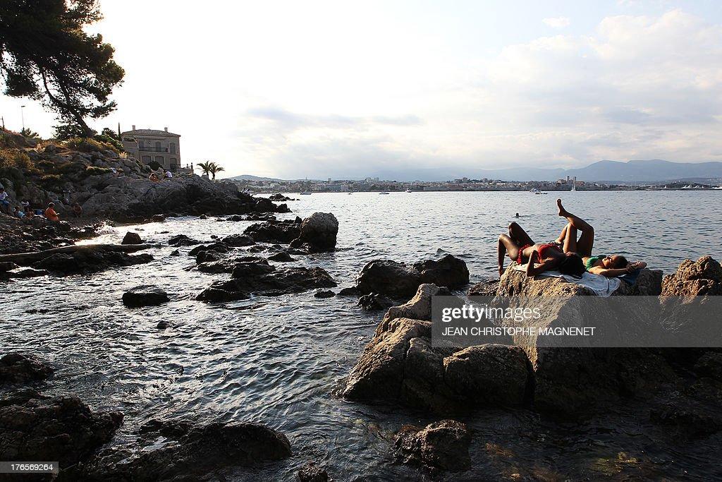 Women sunbathe in Antibes, southeastern France on August 15, 2013.