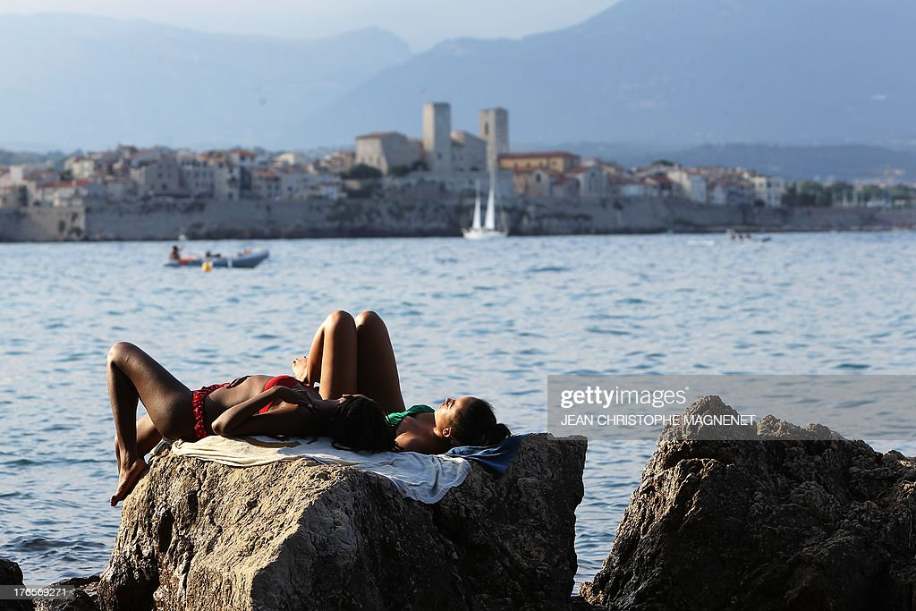 Women sunbathe in Antibes, southeastern France on August 15, 2013.