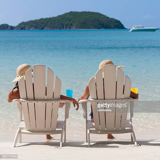 women sunbathing in adirondack chairs at a Caribbean beach