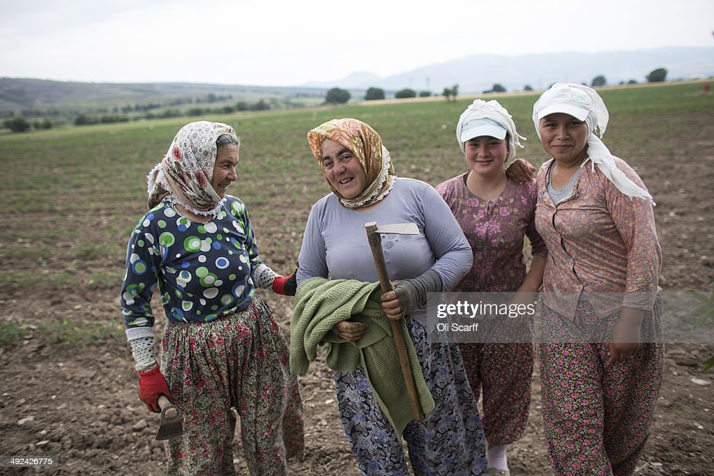 Women take a break from planting crops by hand in a field near the town of Soma whose economy relies heavily on the mining industry on May 20 2014 in...