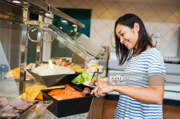 Women take a buffet style meal at Resort Hotel in guam