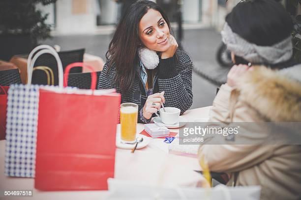 Frauen nehmen Sie einen Kaffee während shopping
