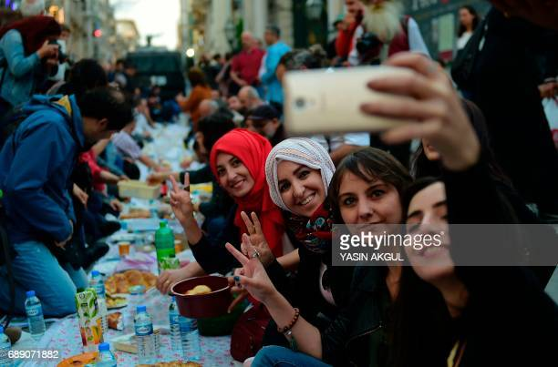 Women take a selfie as people break their fast next to riot police armed with water cannons on May 27 2017 near Taksim Square in Istanbul during the...