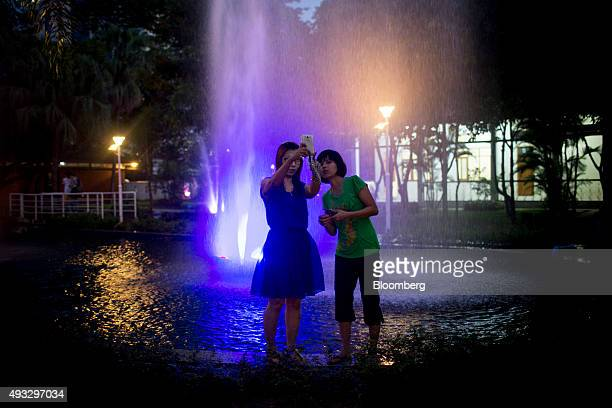Women take a selfie photograph with a smartphone in front of an illuminated water fountain in Maha Bandoola Garden at night in Yangon Myanmar on...
