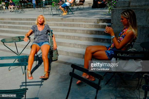 Women take a sunbath at Bryan Park during a sunny day as hot temperatures continue in New York on July 21 2017 / AFP PHOTO / EDUARDO MUNOZ ALVAREZ
