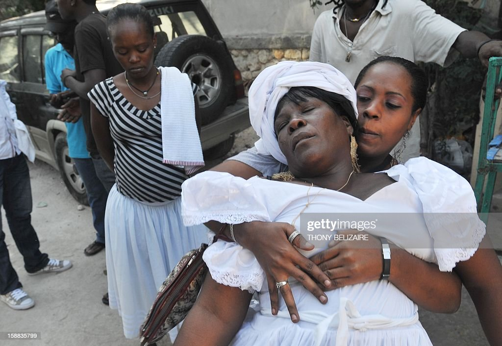 Women take part in a Voodoo ceremony December 30, 2012 in the Petion-ville suburb of Port-au-Prince. The Haitian government declared Voodoo an official religion in 2003, granting Voodoo priests the authority to perform weddings and baptisms. AFP PHOTO/Thony BELIZAIRE