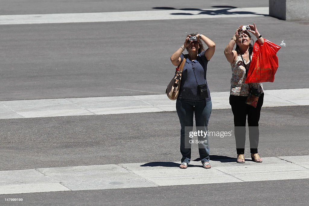Women take photographs of the Catedral de la Almudena on July 7, 2012 in Madrid, Spain. Despite having the fourth largest economy in the Eurozone, the economic situation in Spain remains troubled with their unemployment rate the highest of any Eurozone country. Spain is currently administering billions of euros of spending cuts and tax increases in a bid to manage its national debt. Spain also has access to loans of up to 100 billion euros from the European Financial Stability Facility which will be used to rescue the country's banks that have been badly affected by a crash in property prices.